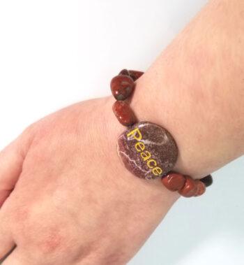 """red jasper """"peace"""" bracelet on wrist"""