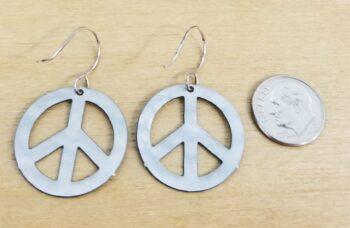 back of peace sign earrings with dime for scale