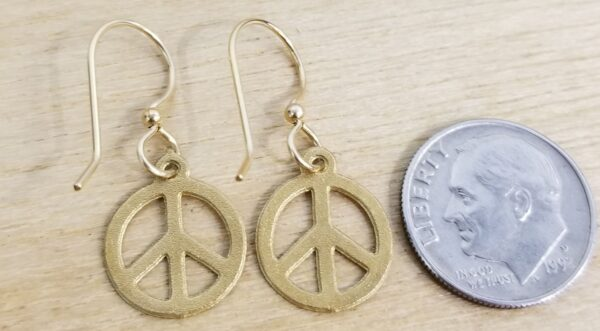 back side of peace sign earrings with dime for scale