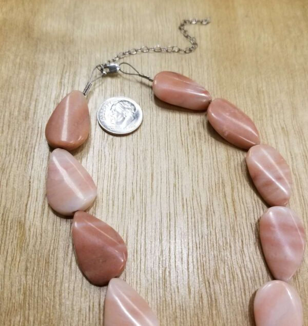 close up of peach jasper necklace with dime for scale