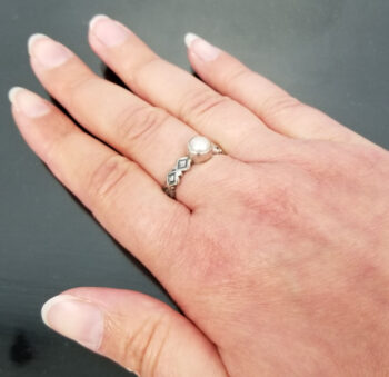 side view of pearl ring with etched silver sides on hand