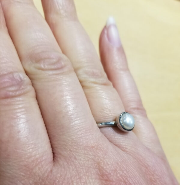 side view of pearl and silver ring on hand