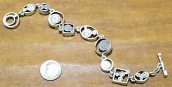 back of Penny Arcade bracelet by Patricia Locke with dime for size