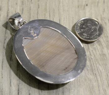 back of handmade petrified wood pendant with dime