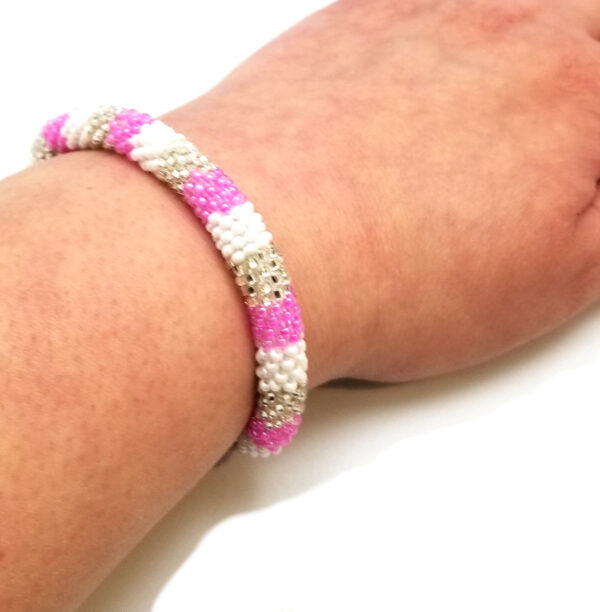 pink, white, and silver-tone roll-on bracelet