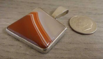 piranha agate pendant with dime for size