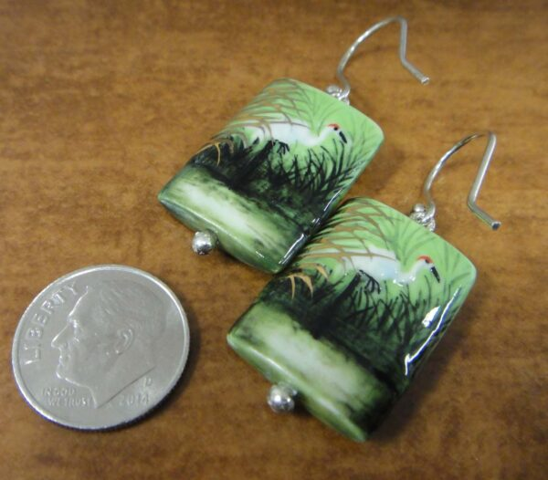back of porcelain heron earrings with dime for scale