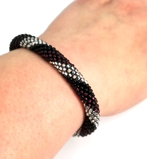 Purple, black, and silver-tone striped roll-on bracelet on wrist