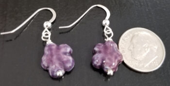 dark purple daisy earrings with dime for scale