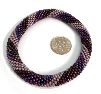 purple striped roll-on bracelet with dime to help judge scale