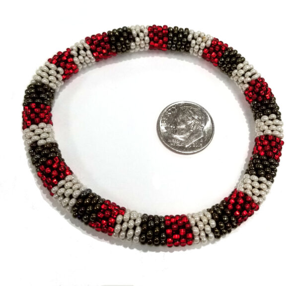 red, bronze, and black striped bracelet with dime for scale