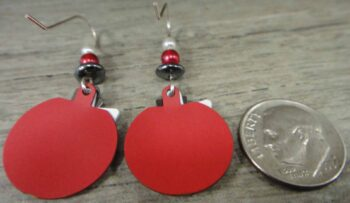 Back of red white and black Adajio earrings with dime for scale
