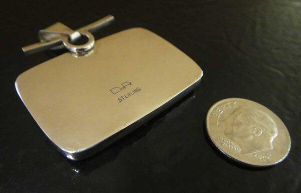 back of red desert jasper pendant with dime for size