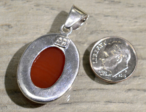 back of handmade red onyx oval pendant with dime for scale