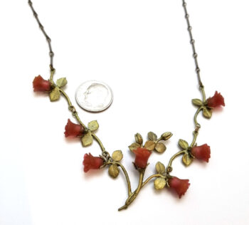 close-up of red rose statement necklace with dime for scale