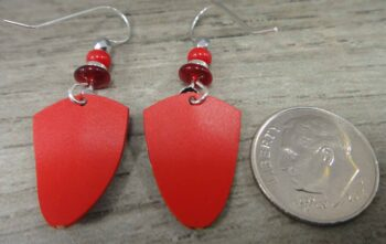 back of red and silvertone swirl Adajio earrings with dime