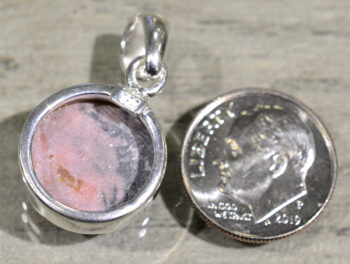 back of pink rhodonite circle shaped pendant with dime for scale