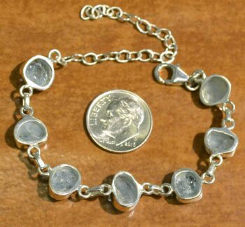 back of handmade rough aquamarine and sterling silver bracelet with dime for size