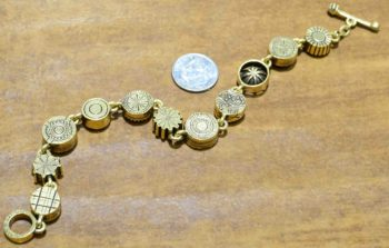 back of Round Two gold tone bracelet by Patricia Locke with dime for size