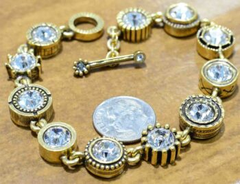 Round Two gold tone bracelet by Patricia Locke with dime for size