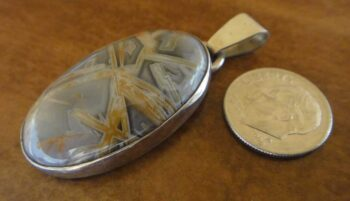 Handmade sagenite and sterling silver pendant shown with dime (not included) for scale