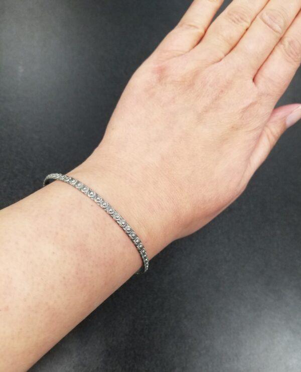 sterling silver daisy bangle bracelet on wrist