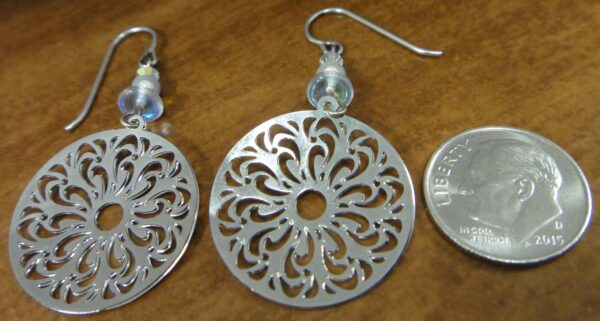 Back of silver-tone filigree circle earrings with dime for scale