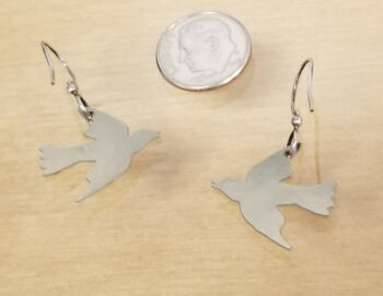 back of bird dangle earrings with dime for scale