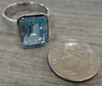 Blue topaz ring with dime for scale