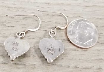 back of southwestern style heart earrings with dime for scale