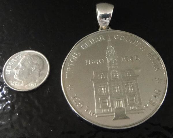 Tipton, Iowa souvenir coin pendant with dime for size