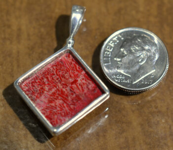 back of handmade red coral pendant with dime