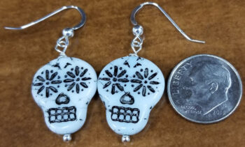 sugar skull earrings with dime for scale