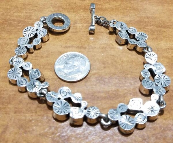 back of Swing silver tone bracelet by Patricia Locke with dime for size