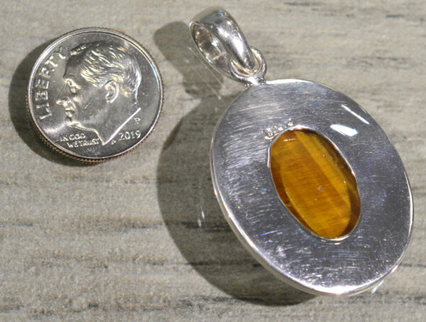 back of handmade oval tiger's eye pendant set in sterling silver with bronze accents with dime for scale