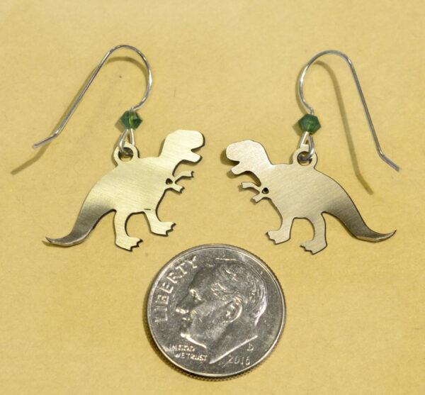 back of green T. rex dinosaur Sienna Sky earrings with dime