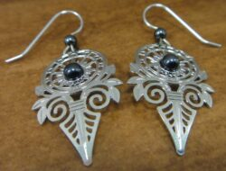 These silver-tone art deco earrings are handmade by Adajio.