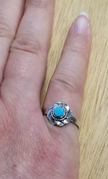 flower ring with turquoise center on hand