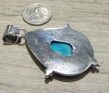 back of turquoise hand hammered sterling silver pendant with dime for scale
