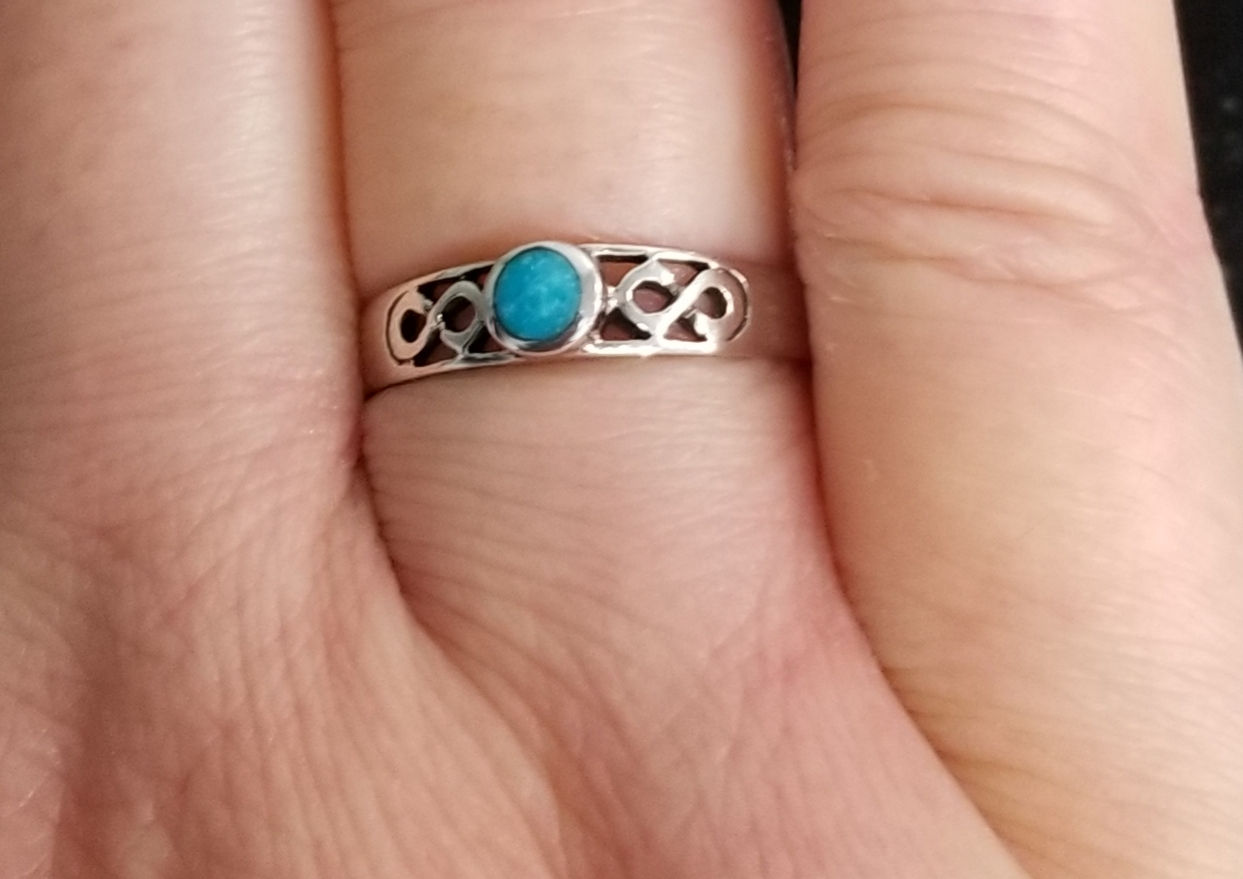 Turquoise infinity ring on hand