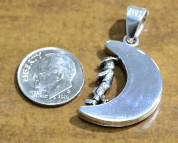 back of turquoise moon and sterling silver cowboy pendant with dime for scale
