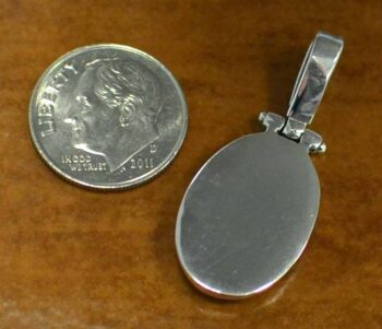 back of turquoise and sterling silver detailed oval pendant with dime
