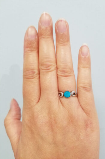 turquoise ring with silver swirls on hand