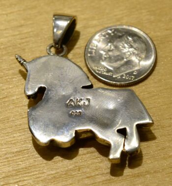 back of sterling silver unicorn with paua shell hooves pendant with dime for scale
