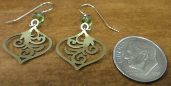 Back of green and multicolored earrings with dime for scale