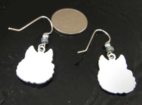 Back of gray and white wolf earrings handmade by Sienna Sky pictured with dime for scale